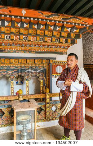 Paro Bhutan - September 10 2016: Local Bhutanese tourist guide wearing traditional clothing standing in front of an altar in a temple.
