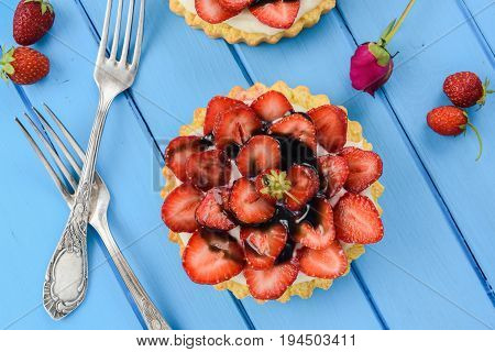 Strawberry tart with mascarpone and licorice syrup served with vintage forks on blue table overhead view