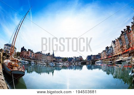 Panoramic view of color Honfleur houses skyline and its reflection in water at sunny day