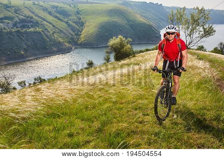 Young athlete cylcist riding mountain cycle on the hill above the river in the countryside. Sportsman dressed in the sportwear, with helmet, red backpack and sportive shoes. Summer landscape like a background. Concept of the helathy lifestyle.