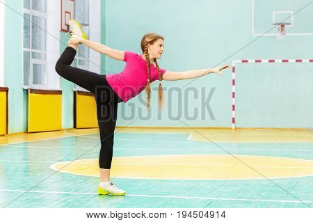 Side view portrait of teenage girl standing on one leg in pose of swallow in gymnasium