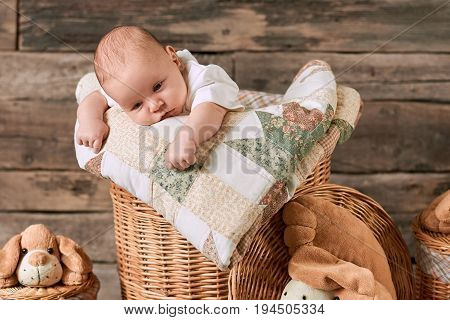 Upset caucasian baby. Basket, blanket and little kid. Can babies feel sad.