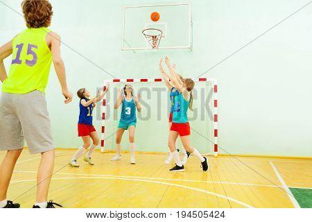 Portrait of teenage team playing basketball in school gymnasium