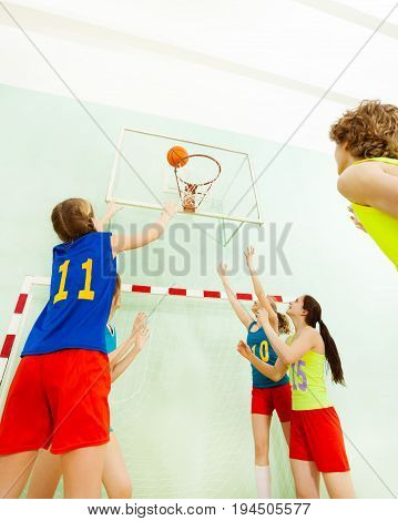 Low angle view of teenage girls playing basketball, throwing the ball into the basket during the match in sports hall