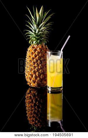 Pineapple With Glass Of Juice On A Black Reflective Background