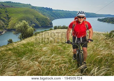 Attractive cyclist riding mountainbike on the meadow above river in summer season in the countryside. Sportsman dressed in the sportwear, with helmet, backpack and sportive shoes. River like a background. Concept of the healthy lifestyle.