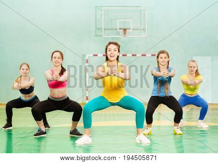 Group of five sporty teenage girls making squats in school gym