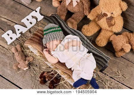 Sleeping kid and teddybears. Child on hay, top view.