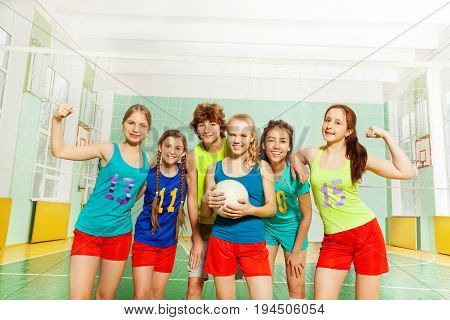Happy volleyball players, teenage boys and girls, standing together in a line after match in sports hall