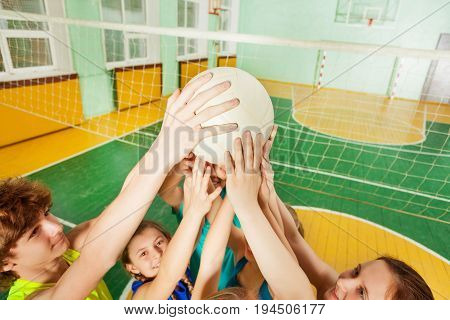 Teenage volleyball team players serving a ball during the match in gymnasium
