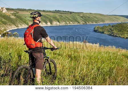 Rear view of the young cyclist stands with mountain bike on the green meadow above big river. Sportsman dressed in the black sportwear, with helmet and red backpack. Beautiful landscape like a background. Concept of the healthy lifestyle.