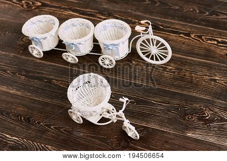 Tricycle flower baskets on wood. White plastic toys. Cheap home decor items.