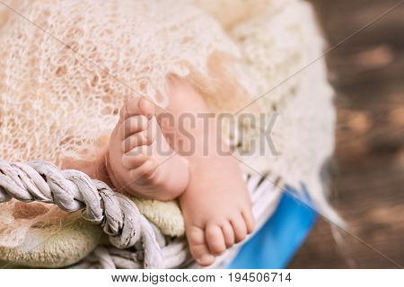 Foot of baby close up. Childish legs and blanket.