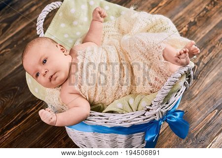 Basket with cute caucasian infant. Little child wrapped in blanket. How to adopt a baby.