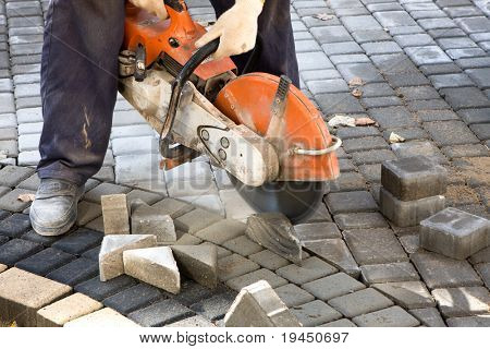 Construction worker making cuttings in concrete blocks for reinforcement using concrete cutter