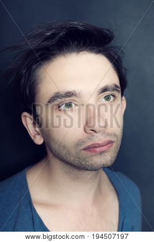 Portrait of young green-eyed man with bristles on his face. Studio photo on black background