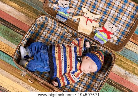 Suitcase with a sleeping baby. Little kid in warm clothes. Born to explore the world.
