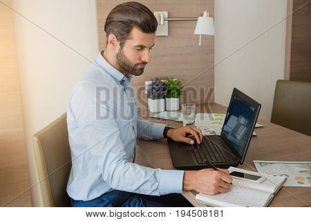 Young male business traveler hotel accomodation working