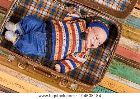 Baby lying in opened suitcase. Little kid wearing spectacles. Smart travel strategies.