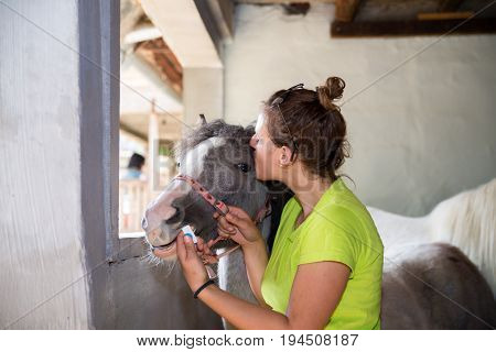 Young veterinarian girl on a farm giving a medicine to a foal and kissing him