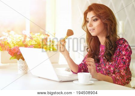 Young woman applying makeup in front of modern laptop