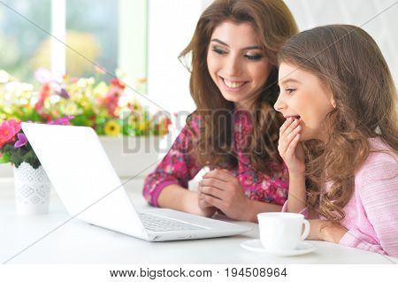 Beautiful  young woman and little girl  sitting at  table and using  laptop