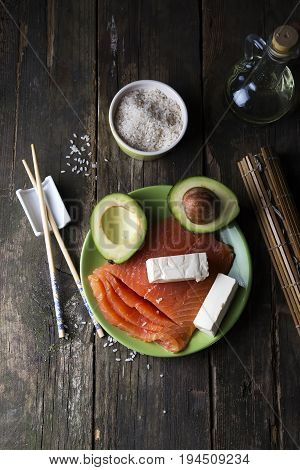 traditional asian ingredients Fresh salmon steak filet, uncooked rice, avocado, sheese on old wooden background