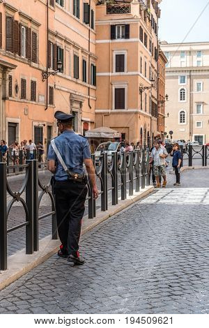 Rome Italy - August 18 2016: Policeman (carabinieri) and tourists in traditional street in the historical centre of Rome. Sunny summer day