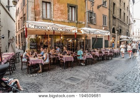 Rome Italy - August 18 2016: Sidewalk restaurant with tourists in Navona square in Rome a sunny summer day.