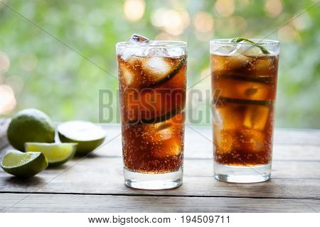 Cuba Libre refreshing summer cocktail with a cola, ice, lime and rum on wooden table with a view to the terrace and trees. Close up summer beverage. Cold longdrink or lemonade.A frozen glass