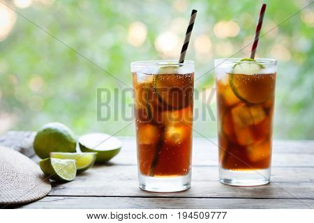Two glasses Cuba Libre or long island iced tea cocktail with a cola, ice, lime, rum with straws on wooden table with a view to the terrace. Close up summer beverage. Cold longdrink or lemonade.