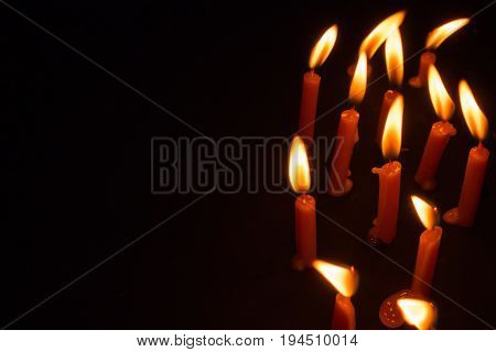 Candles Lit For Prayer On A Black Background With Space For Text