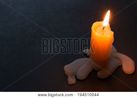 Burning Candle And Wax On A Black Background With Space For Text