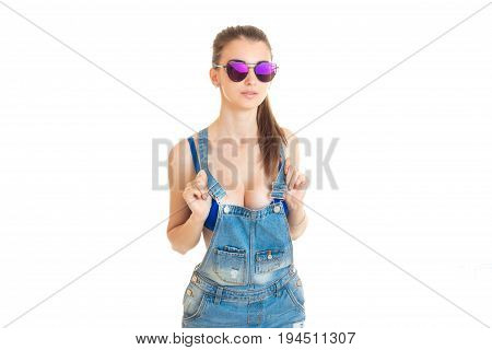 sexy lady in sunglasses and jeans overall with big silicon breasts isolated on white background