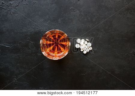 Alcohol In A Glass And A Handful Of Pills On A Black Background