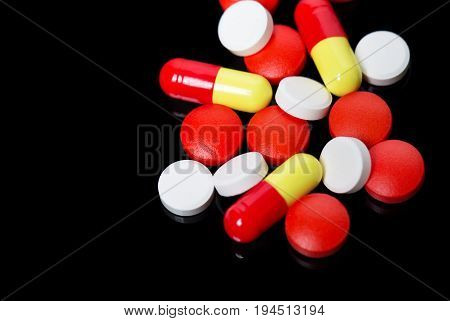 Assorted Pharmaceutical Medicine Pills, Tablets And Capsules Over Black Background.