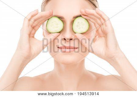 Mature female beauty health care studiio portrait holding cucumbers