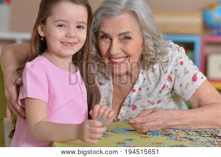Portrait of grandmother collecting puzzle with her granddaughter