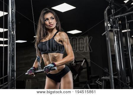 Girl At The Gym Doing Exercise On Triceps. Pulls Rope Handle By Himself On Top