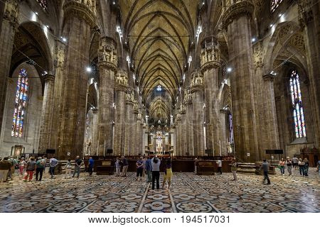 Milan, Italy - May 16, 2017: Tourists are walking inside the Milan Cathedral (Duomo di Milano). Milan Duomo is the largest church in Italy and the fifth largest in the world.