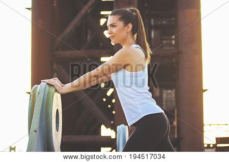 Warming Up Before Jogging. Side View Of Attractive Sporty Woman In Sports Wear Doing Stretching And