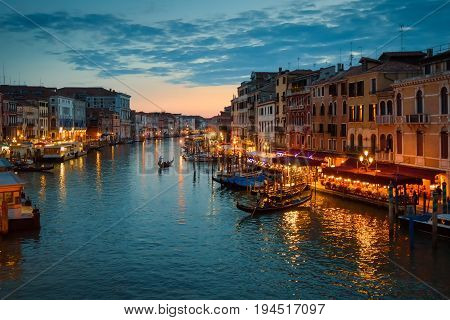 Grand Canal with gondola at night in Venice, Italy. Grand Canal is one of the major water-traffic corridors and tourist attraction in Venice.