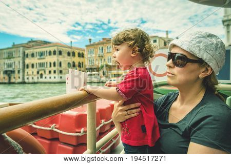 The cute child screams with delight being with his mother on a tourist boat on the Grand Canal in Venice. Grand Canal is one of the major water-traffic corridors and tourist attraction of Venice.
