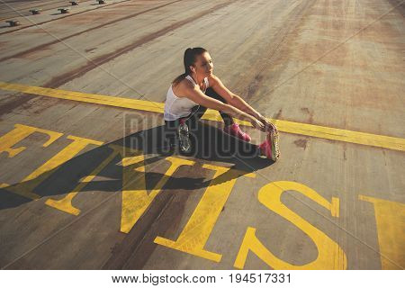 Warming Up. High Angle Side View Of Attractive Young Woman In Sports Wear Doing Stretching And Smili