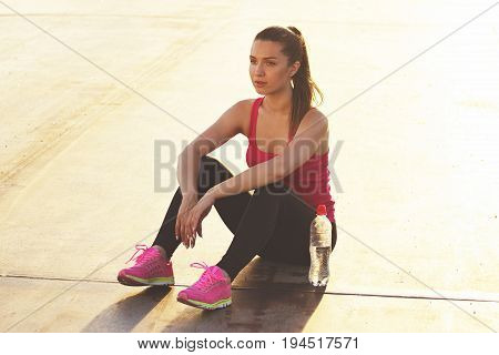 Relaxing After Jogging. Horizontal Shot Of Beautiful Young Woman In Sports Clothing Looks Concentrat