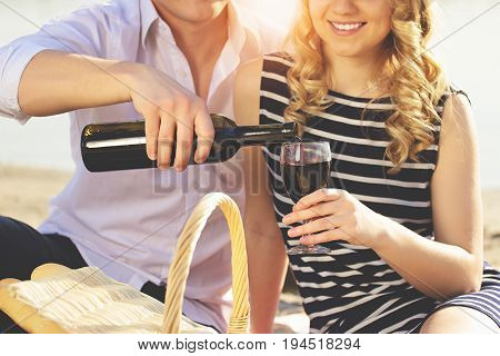 Enjoying Picnic Time Together. Close-up Of Man In Casual Clothes Pouring Wine Into Glass While Sitti