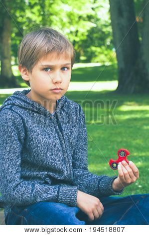 Boy playing with a fidget spinner outdoors