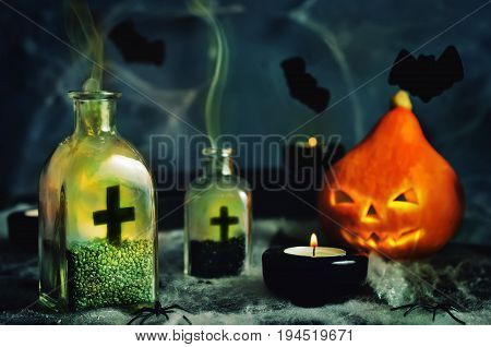Halloween horror background with a spider's web; pumpkin, candles, potions and bats