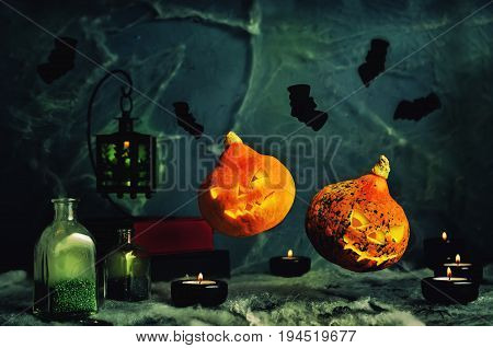 Halloween horror background with flying pumpkins, spider's web, candles, potions and bats