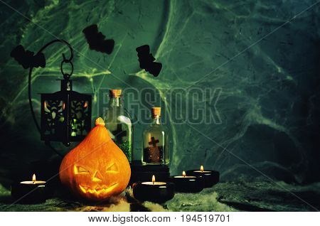 Halloween horror background with a spider's web pumpkin, candles, potions and bats